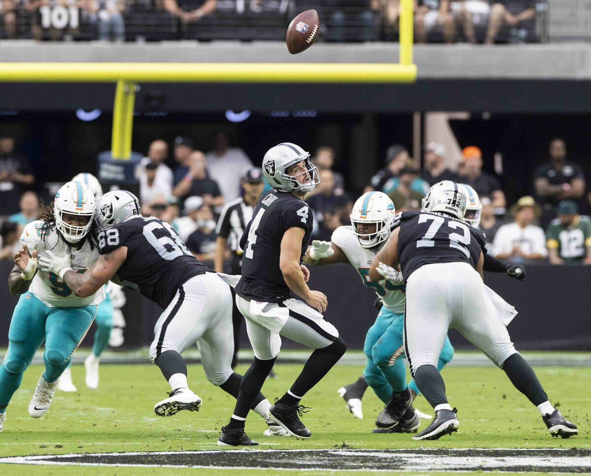 Las Vegas Raiders quarterback Derek Carr (4) looks back at an errant snap In the first half dur ...