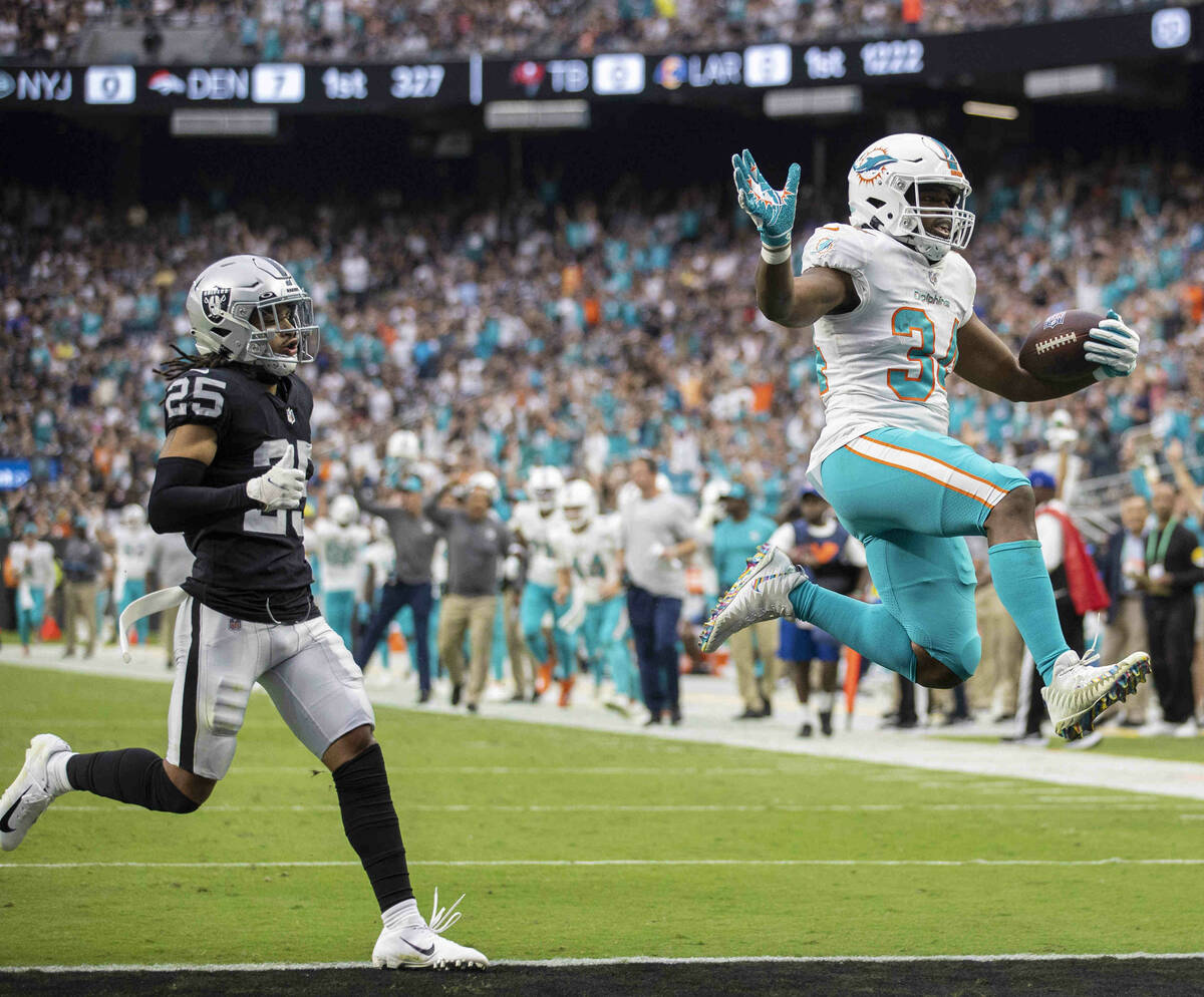 Miami Dolphins running back Malcolm Brown (34) leaps into the end zone past Las Vegas Raiders s ...