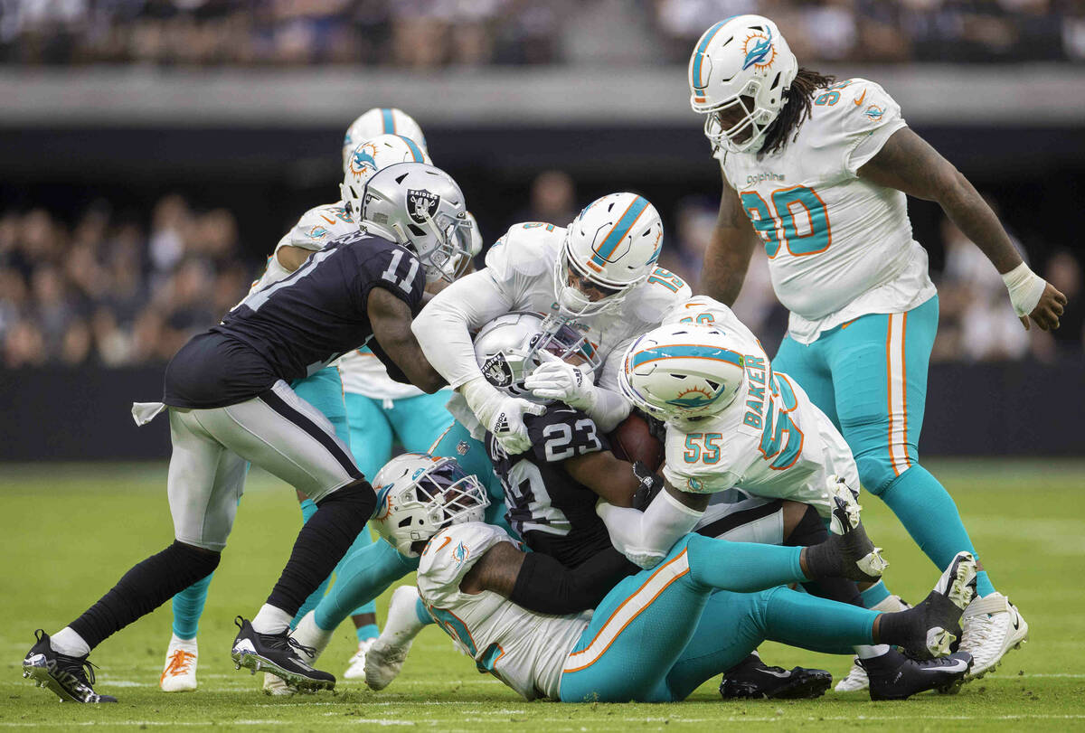 Las Vegas Raiders running back Kenyan Drake (23) is gang tackled by Miami Dolphin defenders in ...