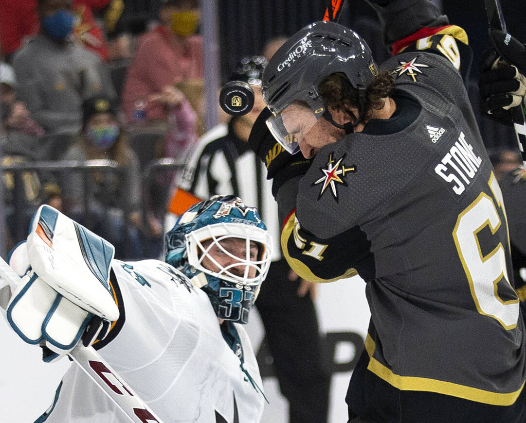 The puck is in the air after hitting the ear of Golden Knights right wing Mark Stone (61) takes ...