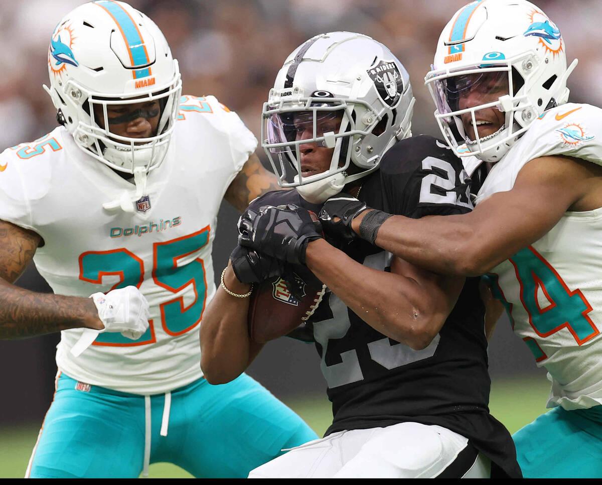 Las Vegas Raiders running back Kenyan Drake (23) is tackled by Miami Dolphins cornerback Xavien ...