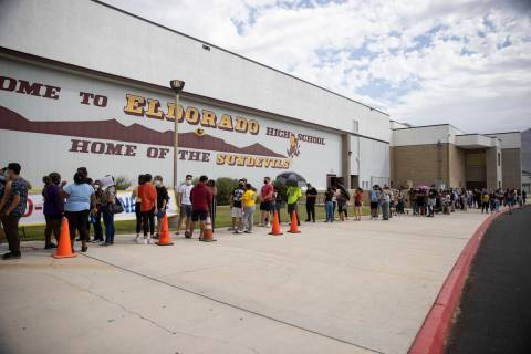 People line up during a pop-up COVID-19 vaccination clinic at Eldorado High School in Las Vegas ...