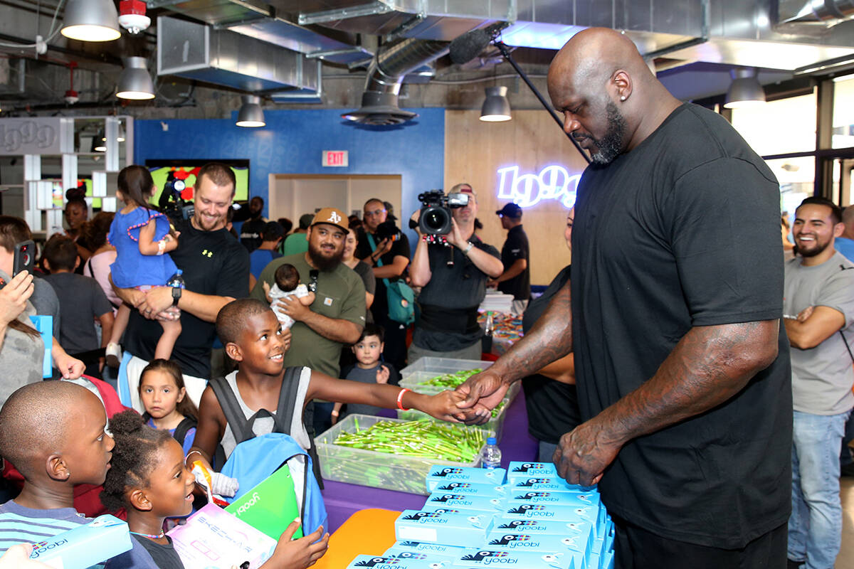 Mishawn Ricks, 9, of Las Vegas, shakes hands with former NBA star Shaquille O'Neal during Shaq- ...