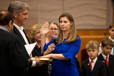 Judge Veronica Barisich is sworn in by Honorable Michael Cherry, while standing with her husban ...