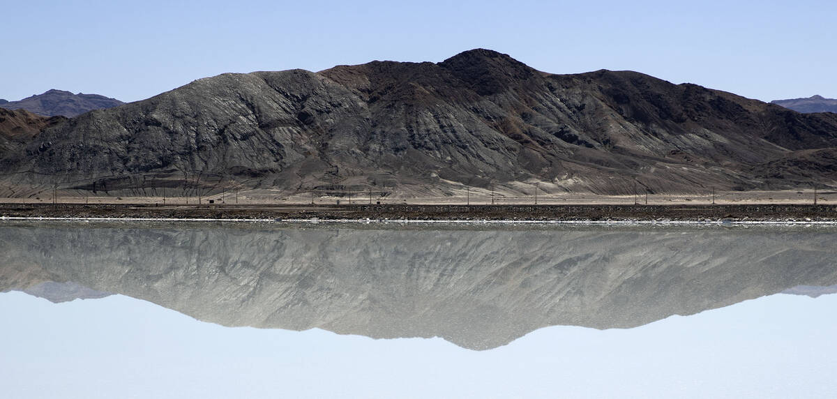 A mountain is reflected in a lithium brine evaporation pond at Albemarle's lithium mine in Silv ...