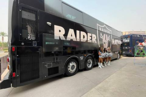 Three Raiderettes stand in front of RTC bus decked out in a Raiders wrap that is part of the RT ...