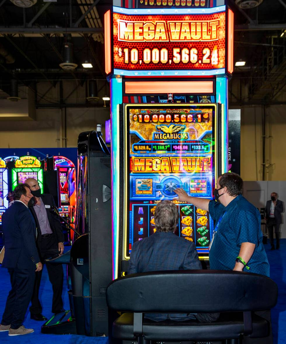Dan Digre, left, gets a visual tour of an IGT Mega Vault game from Tyson Brandes during day 3 a ...