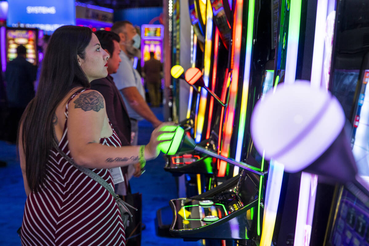 Attendees play slot games in the IGT display space during day 3 at the Global Gaming Expo 2021 ...