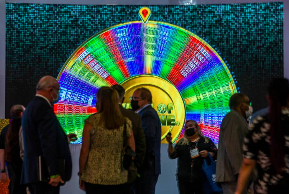 A giant Wheel of Fortune spins as attendees gather in the IGT gaming space during day 3 at the ...