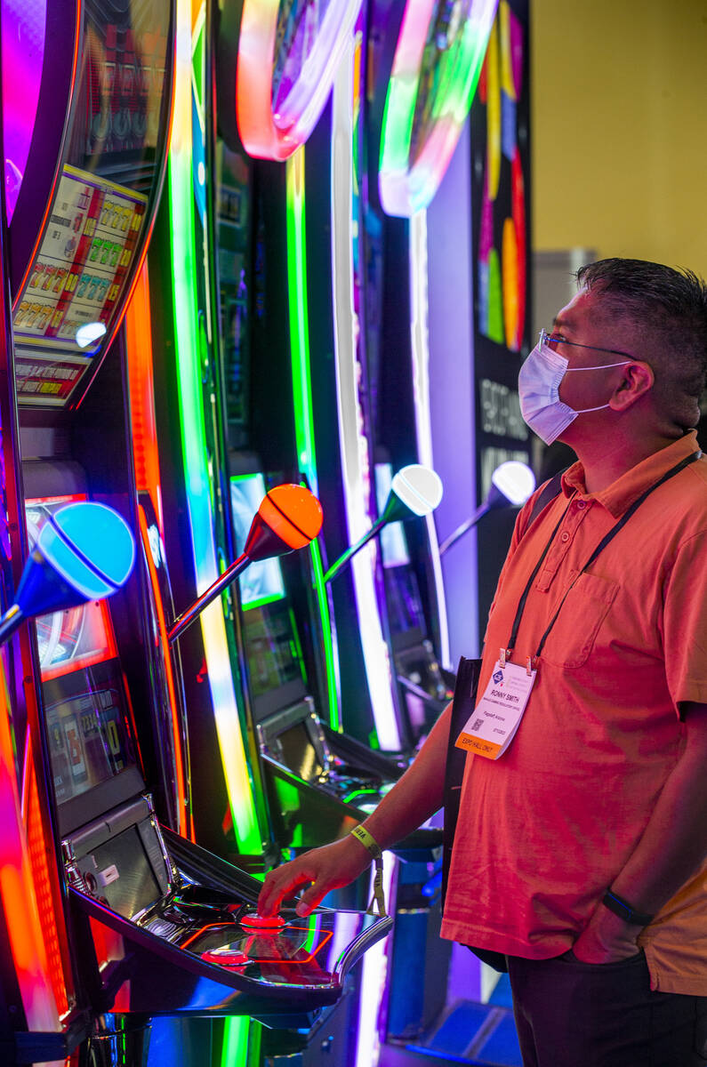 Attendee Ronny Smith plays a slot game in the IGT display space during day 3 at the Global Gami ...