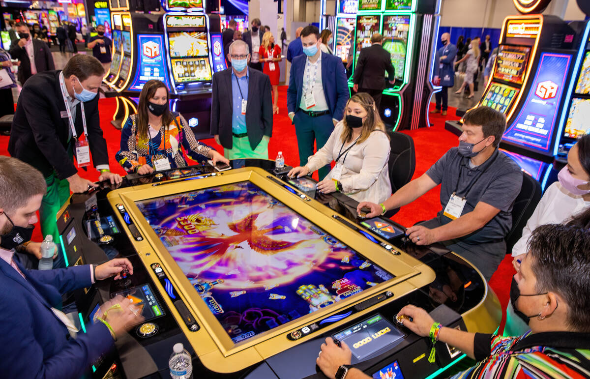 Attendees try out the new Ocean Phoenix game by Gaming Arts during day 2 of the Global Gaming E ...