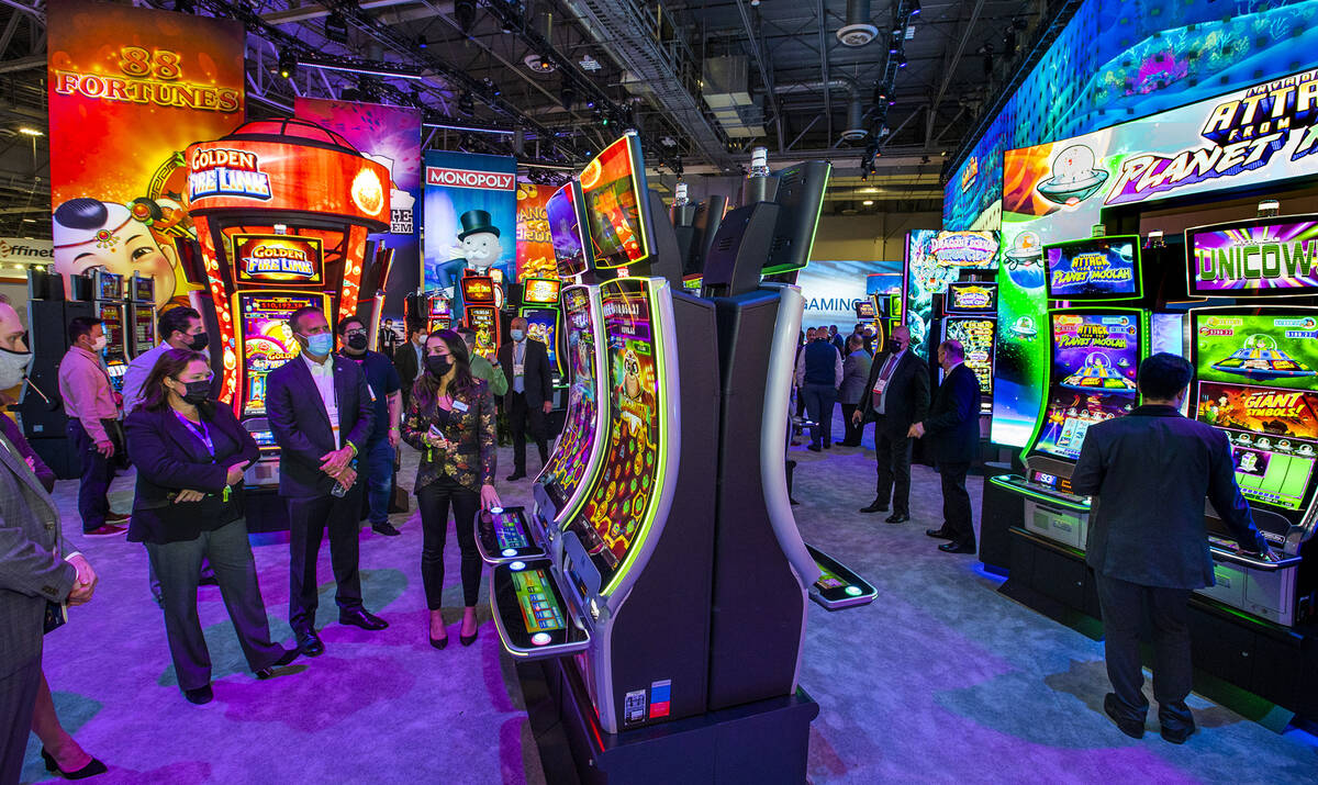 Attendees learn about the newest slot within the Scientific Games Corp. display area during day ...