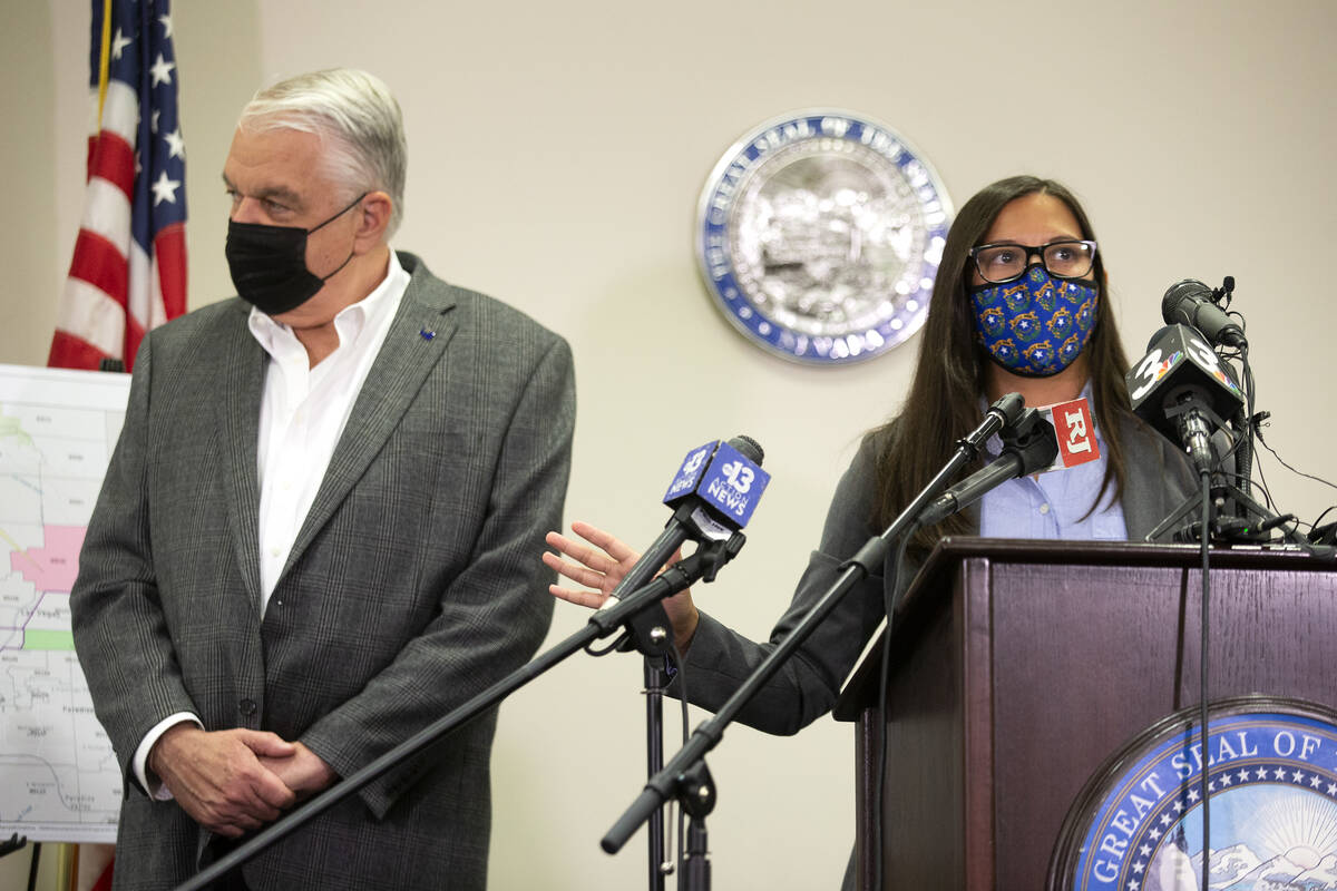 Gov. Steve Sisolak stands next to Incident Commander Sharone Luce during a press conference abo ...