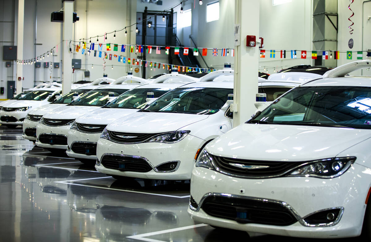 Modified Pacificas are parked in the open warehouse within the Motional autonomous vehicle head ...