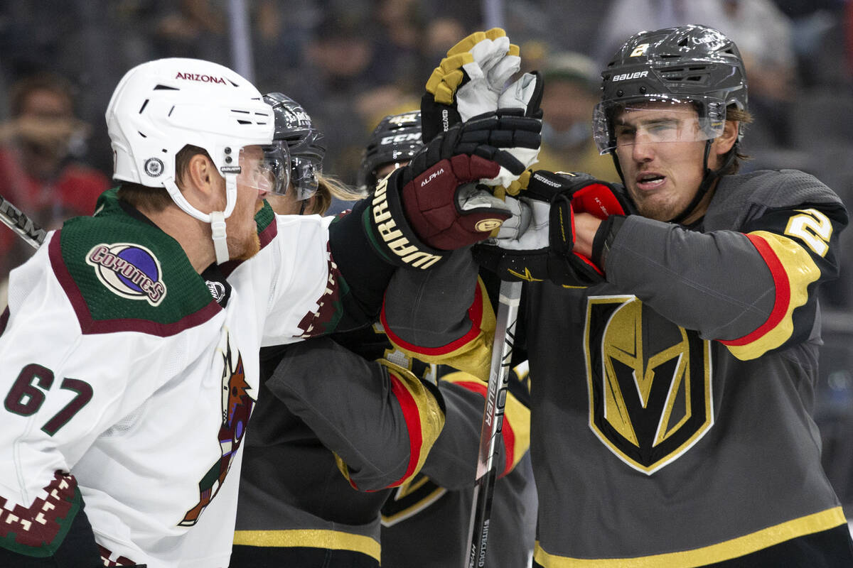 Golden Knights defenseman Zach Whitecloud (2) blocks a punch from Coyotes near  helping  Lawson Crou ...