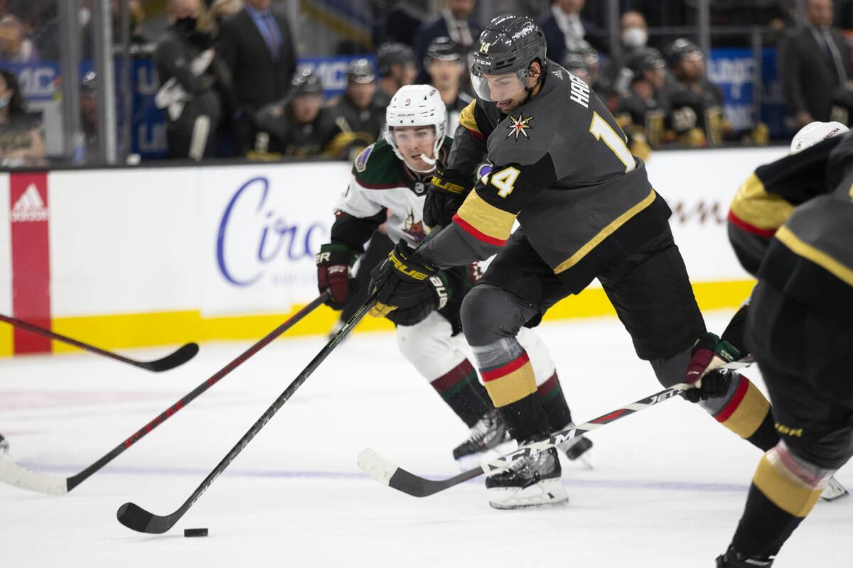 Golden Knights defenseman Nicolas Hague (14) and Coyotes close    helping  Clayton Keller (9) skate fo ...