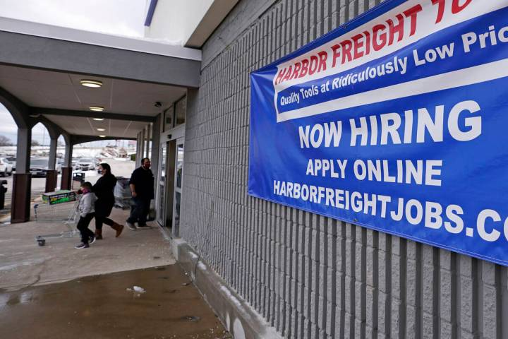 """In this Dec. 10, 2020, file photo, a """"Now Hiring"""" sign hangs on the front wall of a Harbor Frei ..."""
