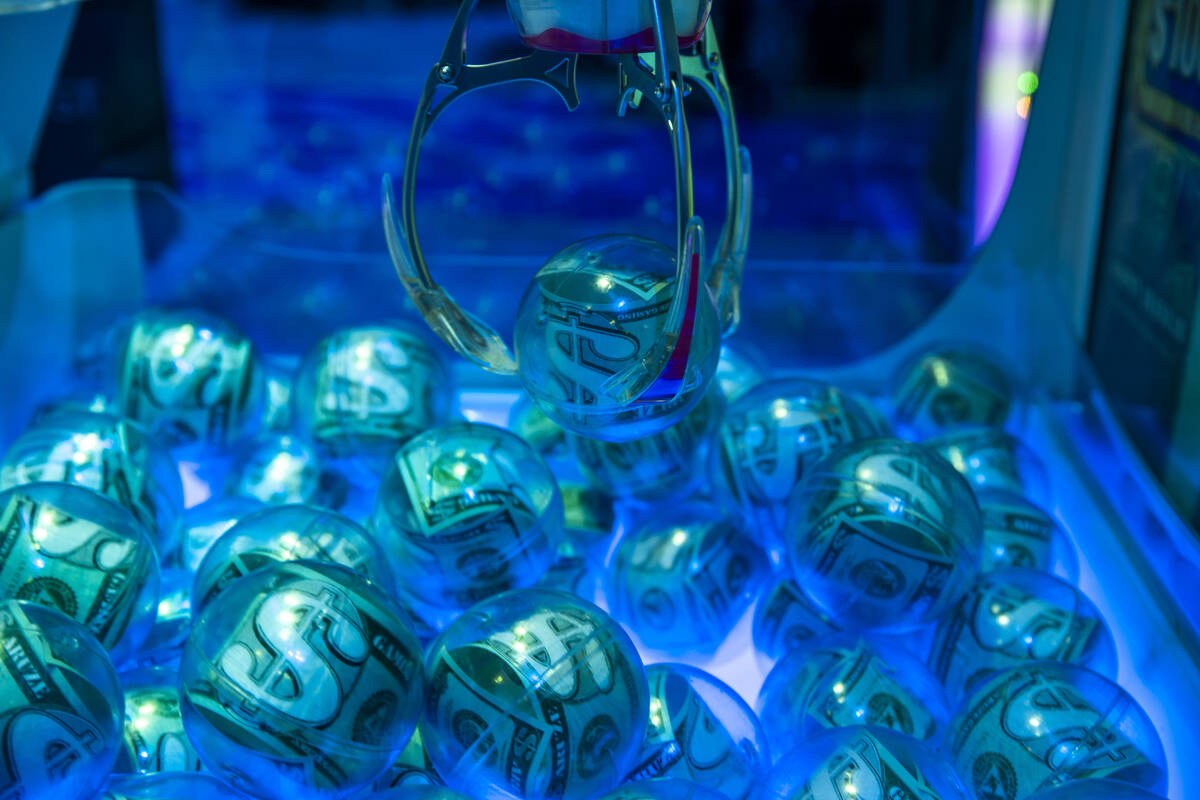 A money ball is grabbed by a claw in an electronic game within the Aruze Gaming display area du ...