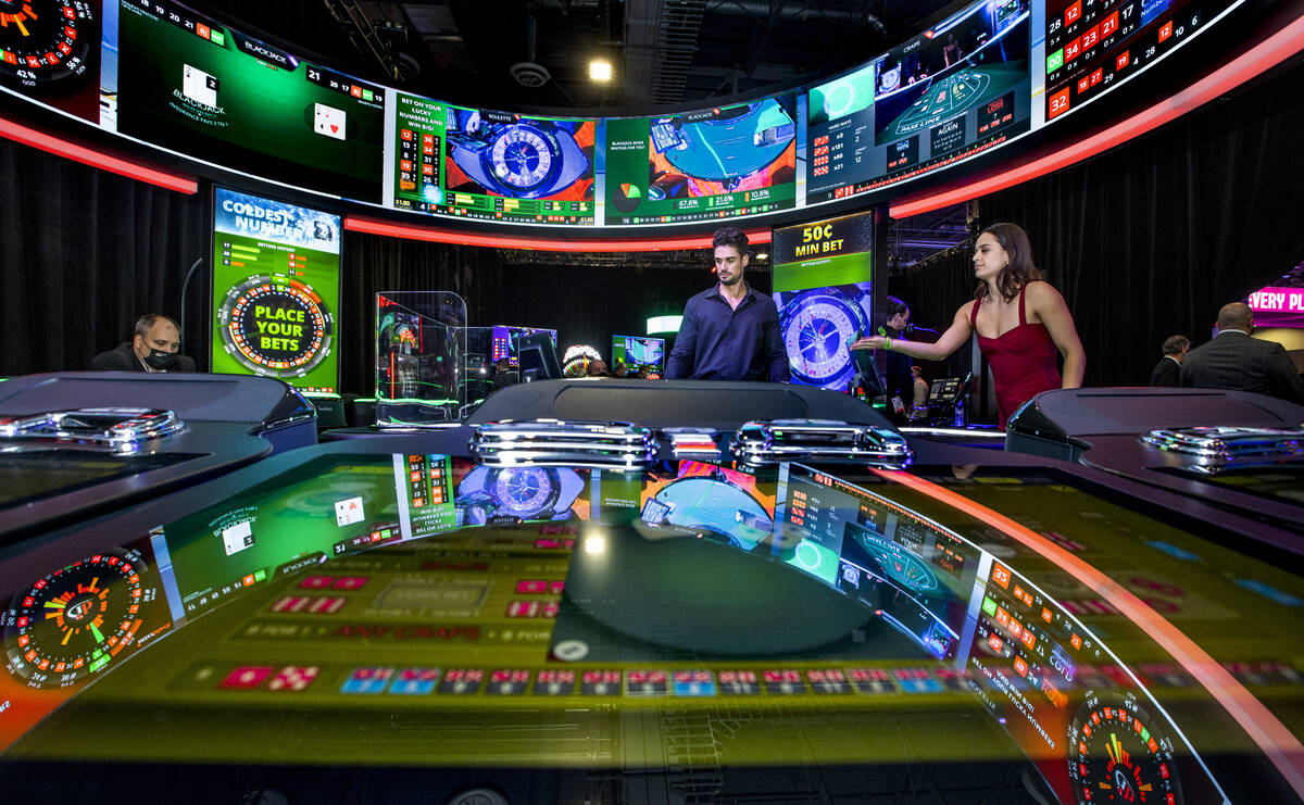 Dina Auneau, right, throws the dice as Liam Black works the craps table about the Interblock Pu ...
