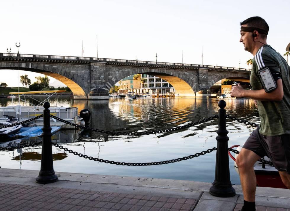 A runner jogs past London Bridge on Sunday, Oct. 3, 2021, in Lake Havasu, Ariz. (Bizuayehu Tesf ...