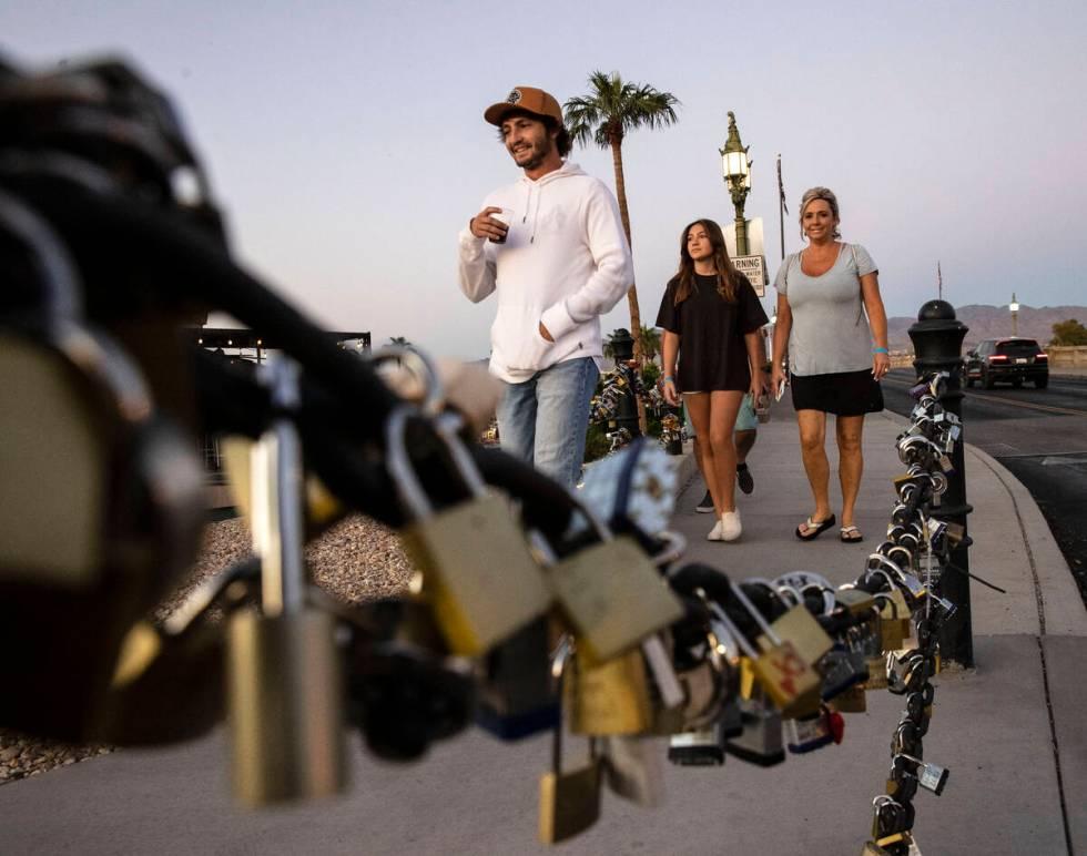 Love padlocks left by visitors are seen as pedestrians walk across London Bridge on Saturday, O ...