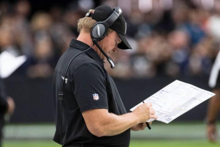 Raiders head coach Jon Gruden checks his playbook during the second half of an NFL football gam ...