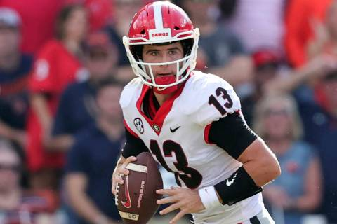Georgia quarterback Stetson Bennett (13) rolls out to pass against Auburn during the first half ...