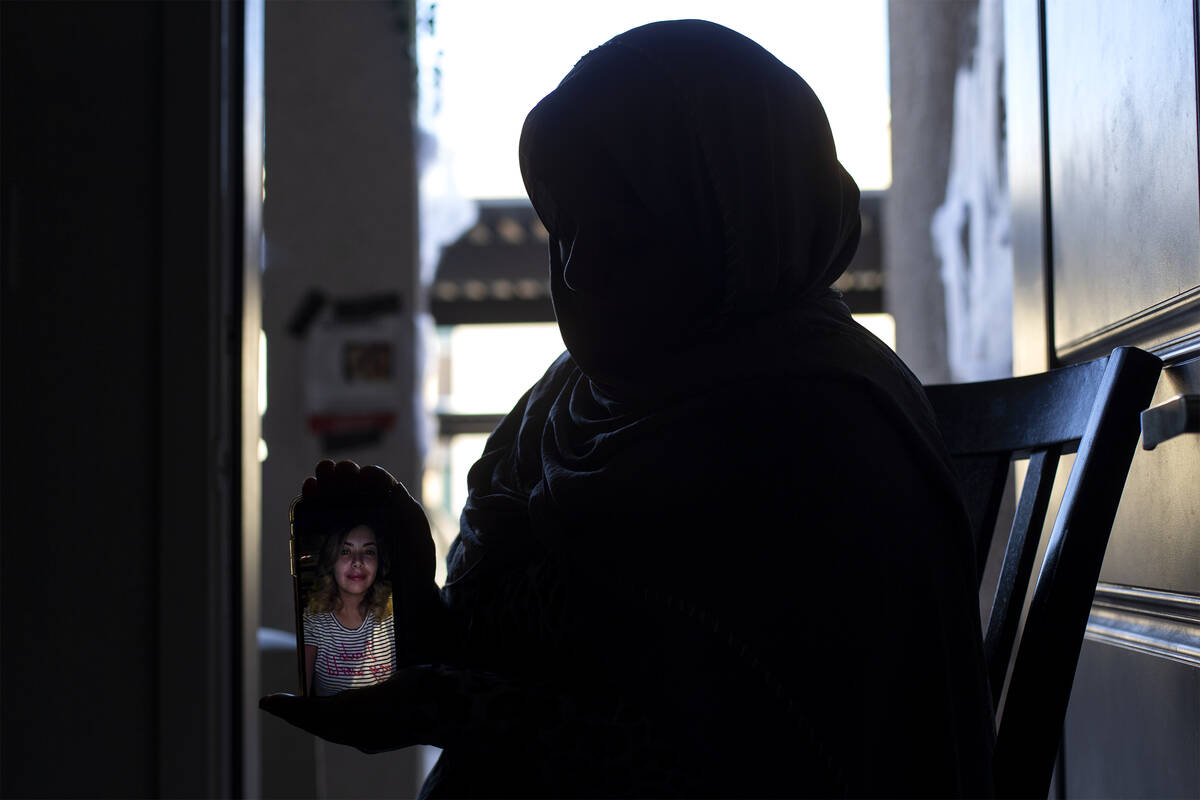 Mrs. Hejji, mother of Jawaher Hejji, holds a photograph of her late daughter at her daughter Ma ...