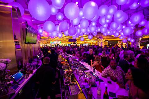 People drink and mingle at GatsbyÕs cocktail lounge during the opening night of Resorts Wo ...