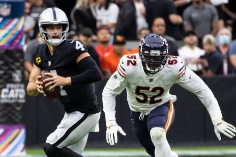 Raiders quarterback Derek Carr (4) chased by Chicago Bears outside linebacker Khalil Mack (52) ...