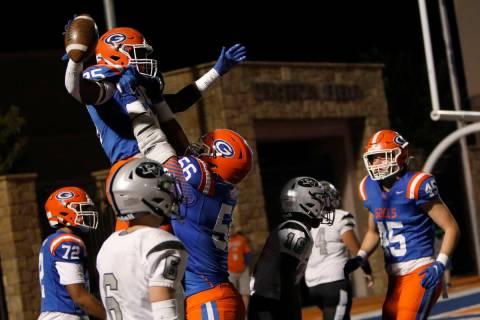 Bishop Gorman High School's William Stallings (25), top, celebrates his touchdown with Zak Yama ...