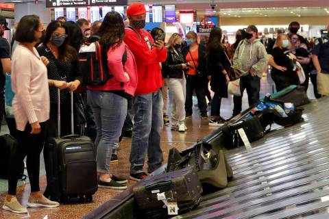 Arriving passengers await their bags in the baggage claim area of McCarran International Airpor ...