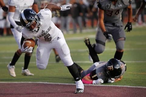 Desert Pines High School's Ferrari Busby (6) scores a touchdown over Faith Lutheran School's Ja ...