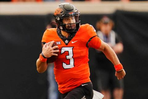 Oklahoma State quarterback Spencer Sanders (3) carries in the first half of an NCAA college foo ...