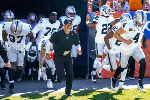 Raiders' interim head coach Rich Bisaccia runs onto the field with his players to face the Denv ...