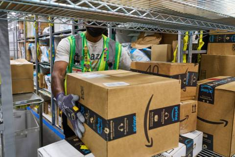A worker handles packages at an Amazon delivery station. Amazon recently opened a new distribut ...