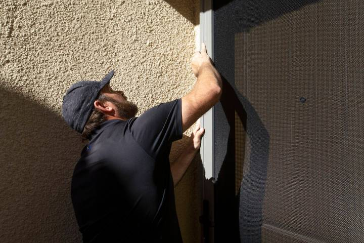 Technician Jed Roehm installs a MeshTec door at a client's home in Sun City Summerlin on Saturd ...