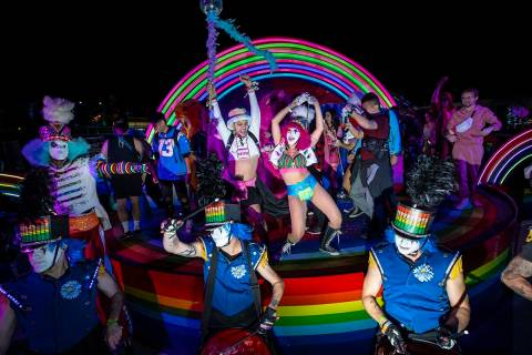 Costumed performers dance and take pictures with attendees during the first day of the Electric ...