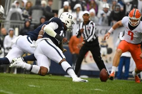 Penn State linebacker Ellis Brooks (13) and Illinois quarterback Artur Sitkowski (9) chase a fu ...