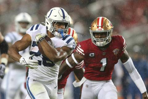 Indianapolis Colts running back Jonathan Taylor, left, runs in front of San Francisco 49ers fre ...