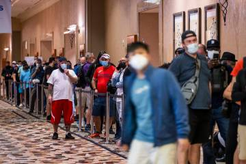 Players in masks wait in line to register for events on the first day of the World Series of Po ...