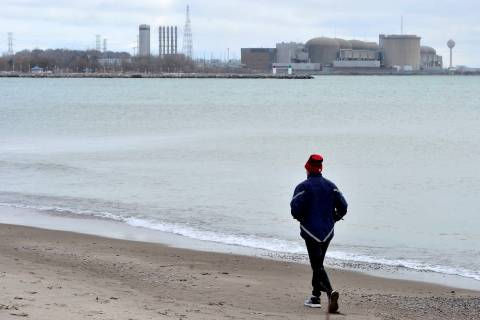 A jogger runs along the beach past the Pickering Nuclear Generating Station, in Pickering, Onta ...