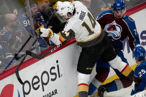 Vegas Golden Knights defenseman Nicolas Hague, left, fights for control of the puck with Colora ...
