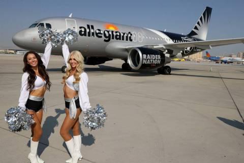 Las Vegas Raiderettes Kristina, left, and Camryn show off Allegiant Air's Raiders-themed aircra ...