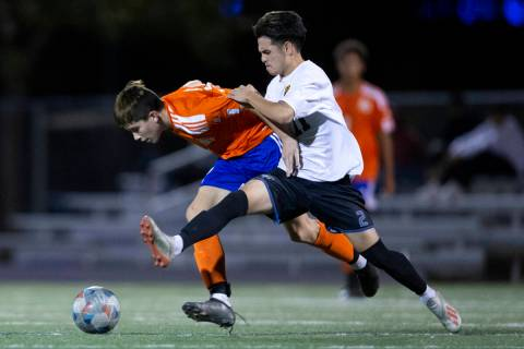 Bishop Gorman's Luke Parker (32) and Las Vegas' Darian Coronel (11) run for the ball during a h ...