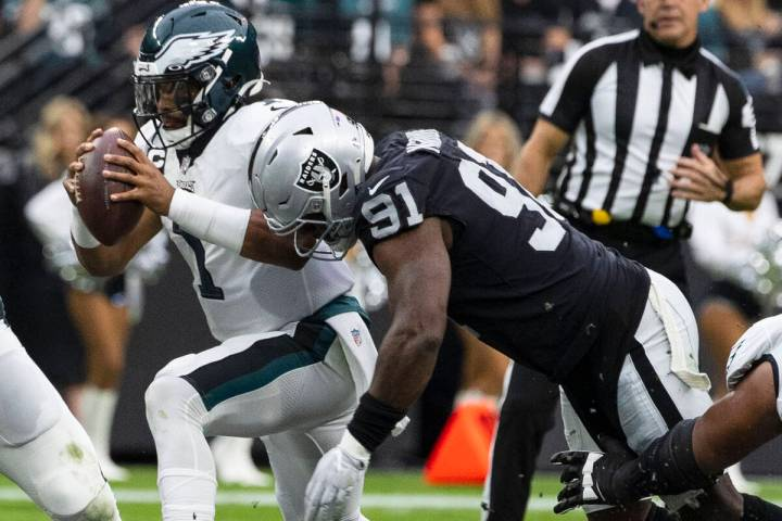 Philadelphia Eagles quarterback Jalen Hurts (1) is sacked by Raiders defensive end Yannick Ngak ...